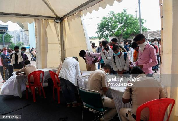 Migrant workers coming from other states stand in queue to register before taking a Rapid Antigen Test for the COVID-19 coronavirus as they arrived...