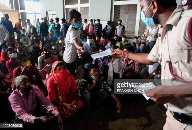 Migrant workers coming from other states wait to get their Rapid Antigen Test report for the COVID-19 coronavirus at the Anand Vihar bus terminal, in...