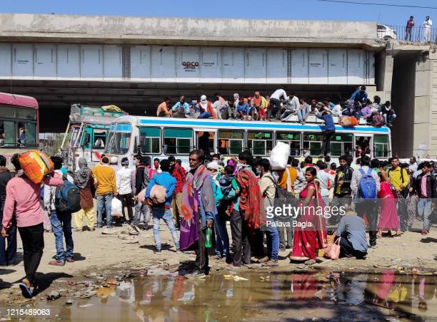 Migrant workers escaping the mega city on foot and then boarding some buses in droves on March 29, 2020 in Ghazibad, India. The local governments...