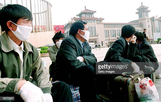 Migrant workers from Heilongjiang province wear masks to protect against the Severe Acute Respiratory Syndrome virus as they wait for a train home at...