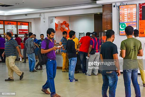 Migrant workers from India look at the exchange rates for Indian rupee at a Ria Money Transfer/Changers stall in Kuala Lumpur Malaysia on November 11...