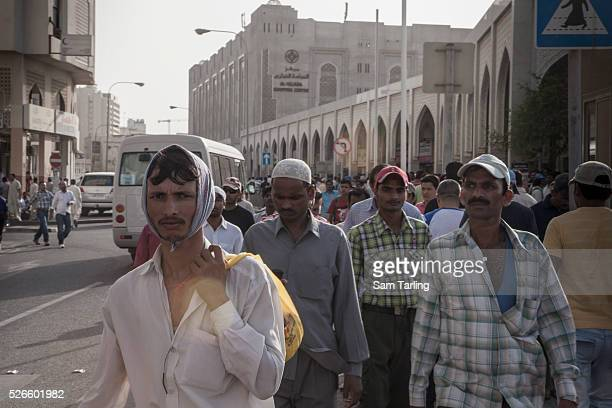 Migrant workers gather on 'Bank Street' in downtown Doha on June 17 where many workers wire remittance money to their families in their home...