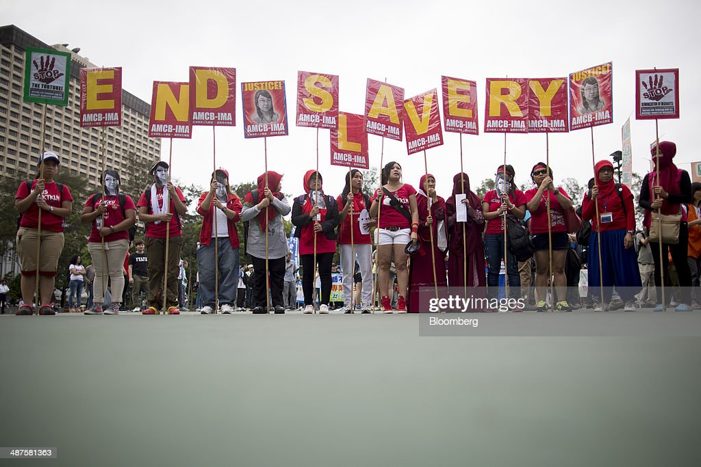 Migrant workers hold signs displaying the words 'end slavery' during a labor day rally in Hong Kong, China, on Thursday, May 1, 2014. Thousands of people have marked labor day by staging a series of rallies to demand better workers' rights. Photographer: Brent Lewin/Bloomberg via Getty Images