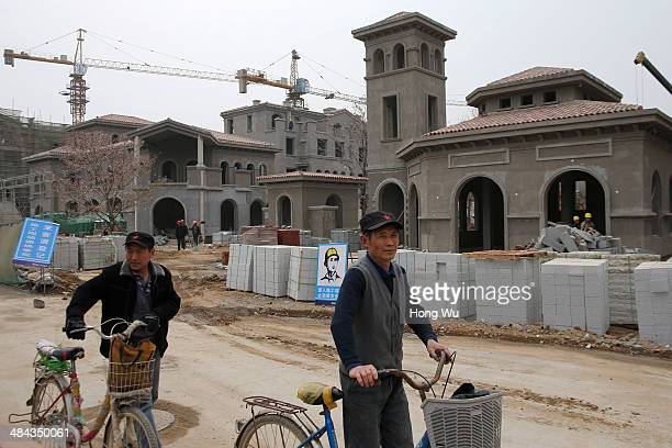 Migrant workers passing by an unfinished townhouse residential area on April 12 2014 in Qingdao China The Chinese government plan to spend 1158...