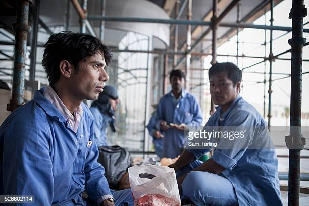 Migrant workers pause to eat at the Sports City area of Doha Qatar on June 18 2011 According to the advocacy group Human Rights Watch hundreds of...