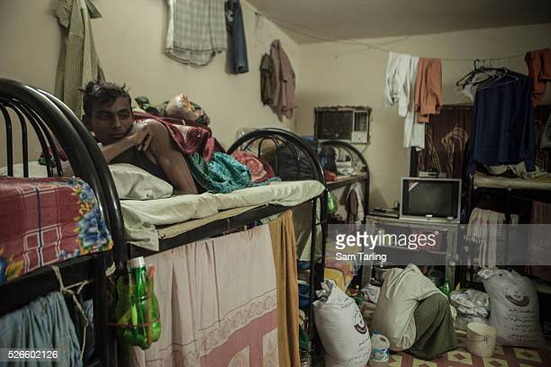 Migrant workers rest after a day of work on foam mattresses between 1 and 8 centimetres thick in a labor camp dormitory in Doha's Industrial Area on...