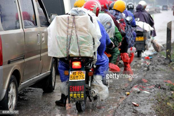 Migrant workers ride motorcycles in the rain ahead to Guangdong on February 4, 2017 in Wuzhou, Guangxi Zhuang Autonomous Region of China. Migrant...