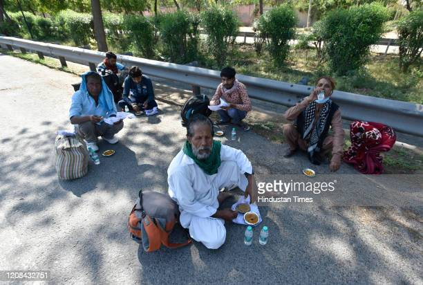 Migrant workers seen having food by the road as they head home on the third day of national lockdown imposed by Prime Minister Narendra Modi to curb...