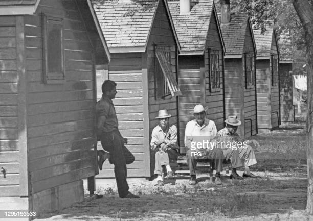 Migrant workers sitting outside a wooden hut at a migrant worker camp in Boulder, Colorado, circa 1955.