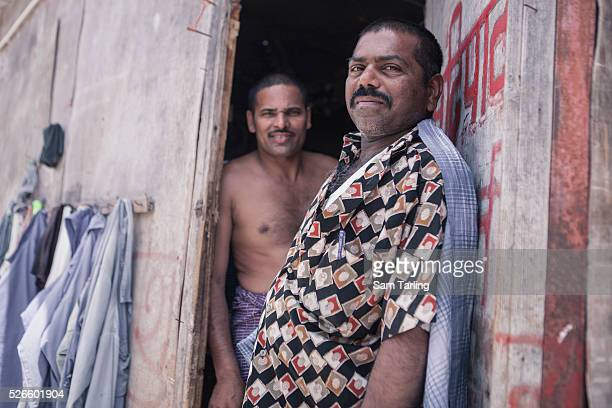 Migrant workers stand in the doorway of their shared bedroom at a workers' camp in alKhor Qatar on June 17 2011 According to the advocacy group Human...