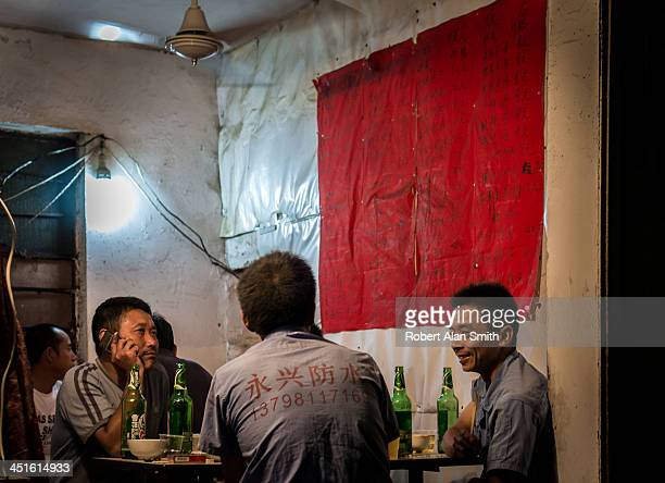 Migrant workers take dinner and drink beer in a small local eatery in Shanghai