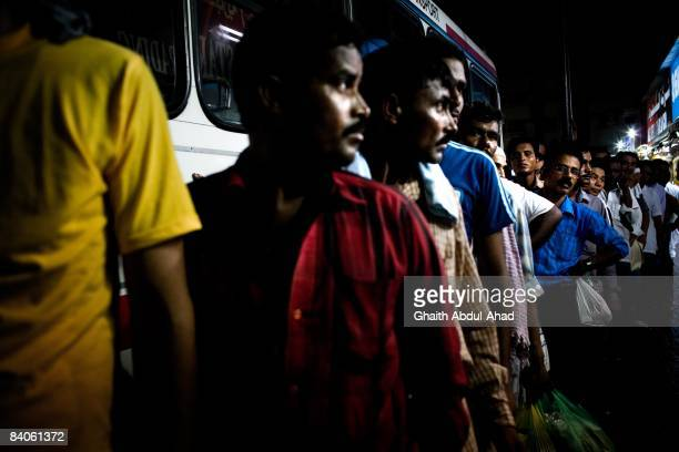 Migrant workers wait in line for a bus to return them to the labor camps located outside the city after a day of work July 19, 2008 in Dubai, United...