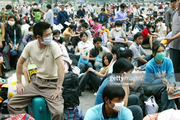 Migrant workers wait outside the train station before returning home because of the worry over SARS May 2, 2003 in Guangzhou, the capital of...