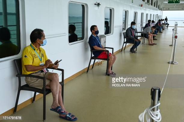 Migrant workers wearing face masks sit on socially distanced seats onboard the SuperStar Gemini cruise ship, currently used to accommodate foreign...