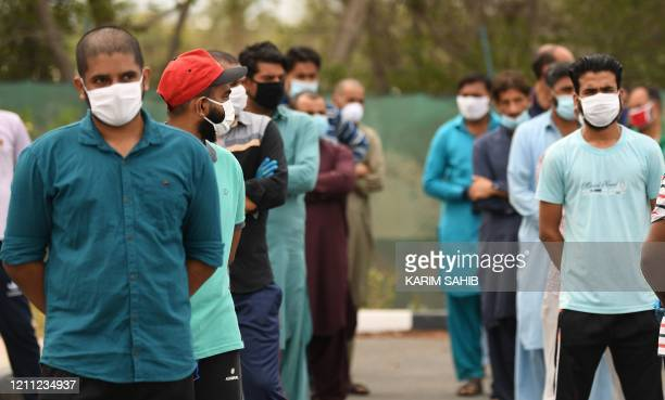 Migrant workers wearing protective masks keep distance from each other to receive Iftar meals during the Muslim holy month of Ramadan within the...