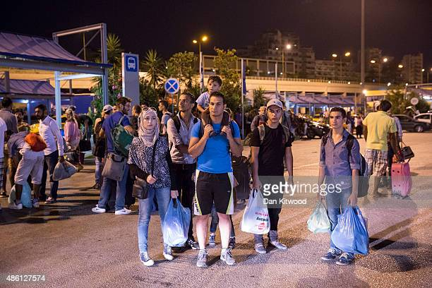 Migrants along with European tourists wait to board a bus heading to Athens Train Station after disembarking a Blue Star ferry from Kos on the Greek...