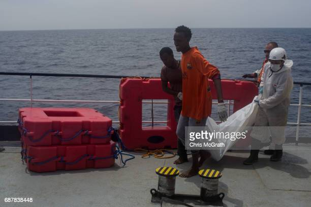 Migrants and crew members from the Migrant Offshore Aid Station 'Phoenix' vessel carry the body of a drowning victim on May 24 2017 off Lampedusa...
