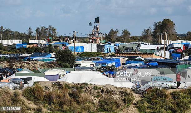 TOPSHOT Migrants and migrantsupporting association members look out from a watchtower at the Jungle migrant and refugee encampment in Calais on...