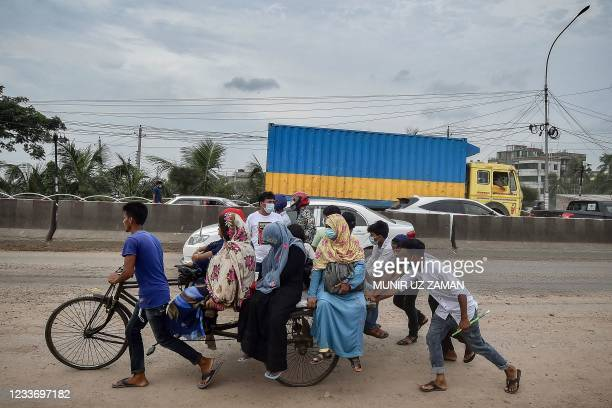 Migrants and other people board a cycle rickshaw cart as they leave for their native places after Bangladesh's authorities ordered a new lockdown to...