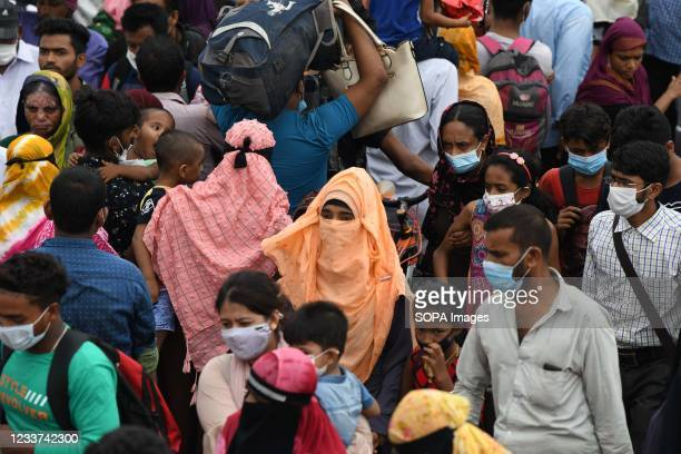 Migrants and other people returning to their native homes crowd to board a ferry as authorities ordered a new lockdown to contain the spread of...