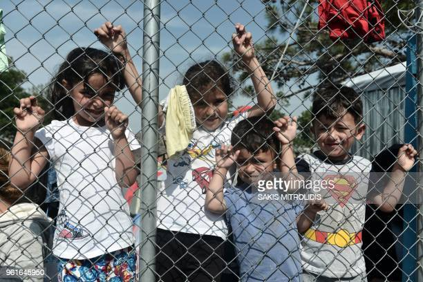 Migrants and refugee children who live in a camp in a suburb west of the northern city of Thessaloniki stand behind a fence as adult hold a protest...