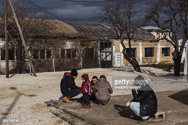 Migrants and refugees and a child wait for a bus at a transit camp in southern Serbian town of Presevo on January 9 2016 More than a million refugees...