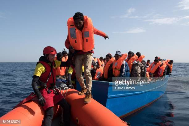 Migrants and refugees are assisted by members of the Spanish NGO Proactiva Open Arms as they crowd on board of a wooden boat sailing out of control...