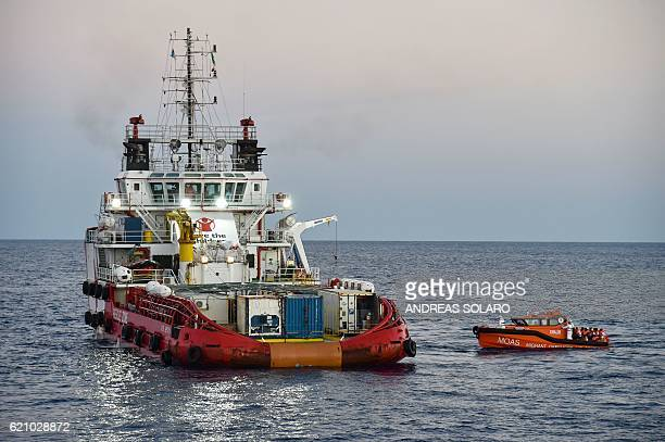 Migrants and refugees are transferred from the Topaz Responder ship run by Maltese NGO 'Moas' and the Italian Red Cross to the Vos Hestia ship run by...
