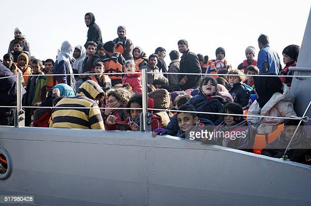 Migrants and refugees arrive aboard a Greek coast guard boat to the port of Mytilene on the Greek island of Lesbos on March 29 after being rescued by...