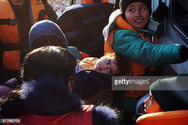 Migrants and refugees arrive aboard a Greek coast guard boat to the port of Mytilene on the Greek island of Lesbos on March 29, 2016. The United...