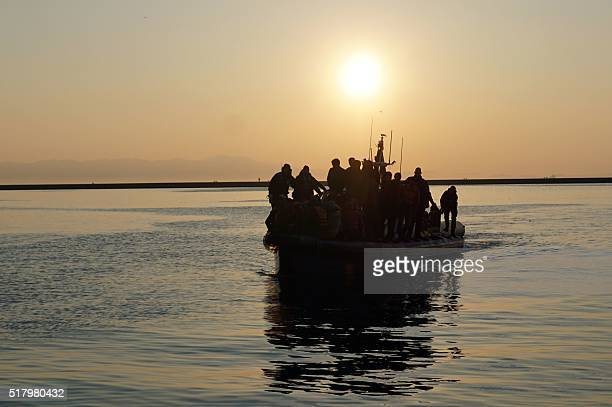 Migrants and refugees arrive aboard a Swedish Frontex patrol boat to the port of Mytilene on the Greek island of Lesbos on March 29, 2016. The United...