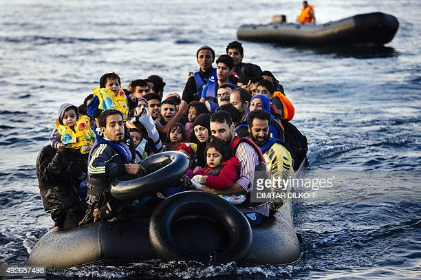 Migrants and refugees arrive on a dinghy on the Greek island of Lesbos after crossing the Aegean sea from Turkey on October 14 2015 More than 400000...