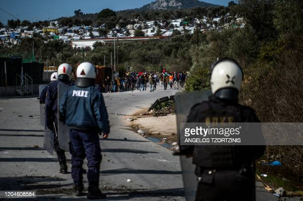 Migrants and refugees block a road near the Moria camp for refugees and migrants during clashes with riot police on the island of Lesbos, on March 2,...