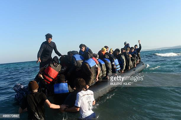 Migrants and refugees board a dinghy to travel to the Greek island of Chios from Cesme in the Turkish province of Izmir on November 4 2015 Migrants...