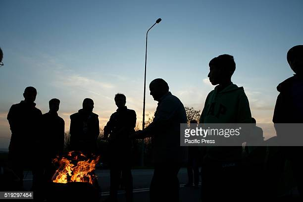 Migrants and refugees build a fire to warm themselves taking part in a road block on the highway near the village of Idomeni close to the...