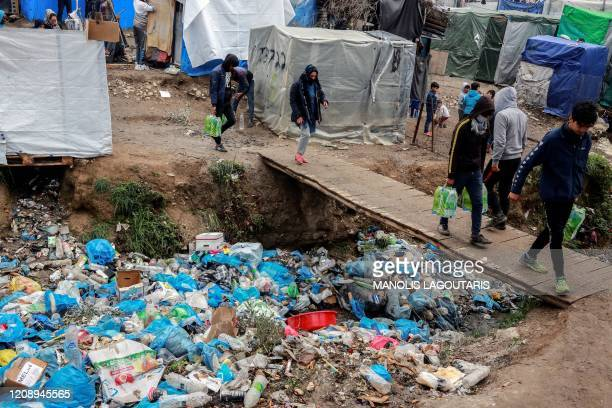 Migrants and refugees carry bags with food as they walk past piles of garbage at a makeshift camp next to the Moria camp on the Greek island of...