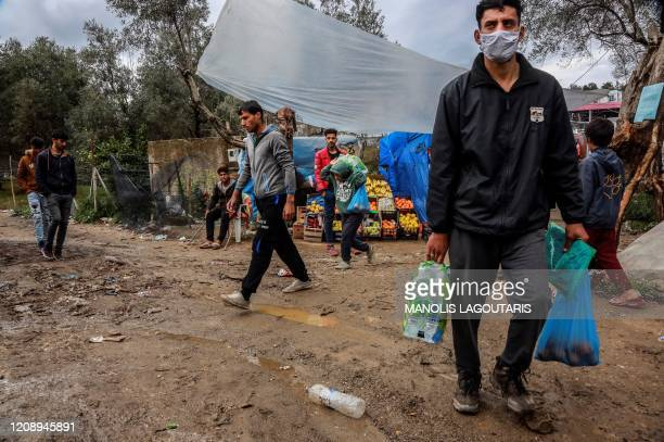 TOPSHOT Migrants and refugees carry bags with food at a makeshift camp next to the Moria camp on the Greek island of Lesbos on April 2 2020 Over 20...