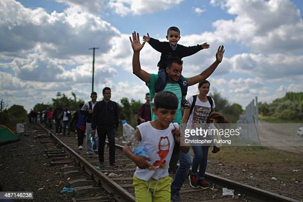 Migrants and refugees celebrate as they cross the border from Serbia into Hungary along the railway tracks close to the village of Roszke on...