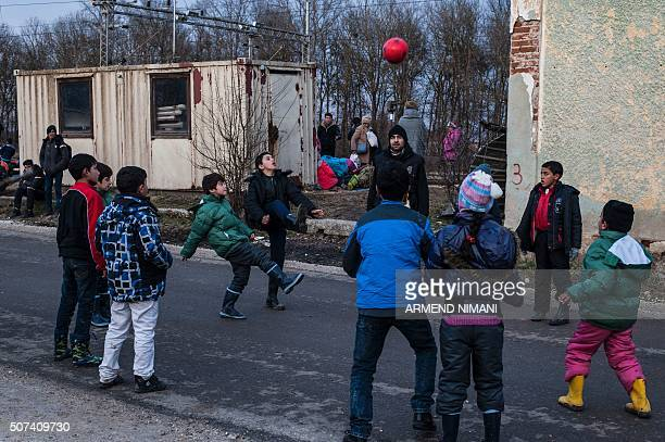 Migrants and refugees children play with a football as they wait for a train after crossing the Macedonian border into Serbia, near the town of...