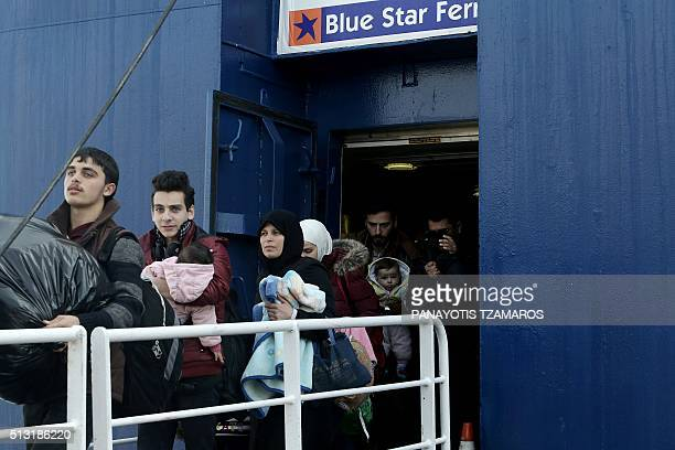 Migrants and refugees disembark from the Diagoras pasenger ship upon their arrival at the port of Piraeus on March 1 2016 More than 131000 migrants...