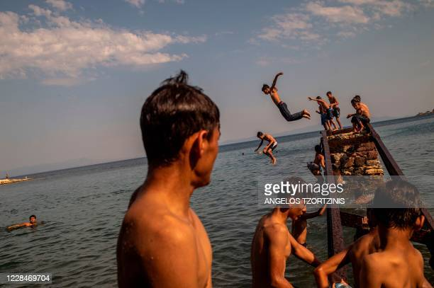 Migrants and refugees enjoy the sea near Mytilene, on the Greek island of Lesbos on September 12 a few days after a fire destroyed the Moria refugee...