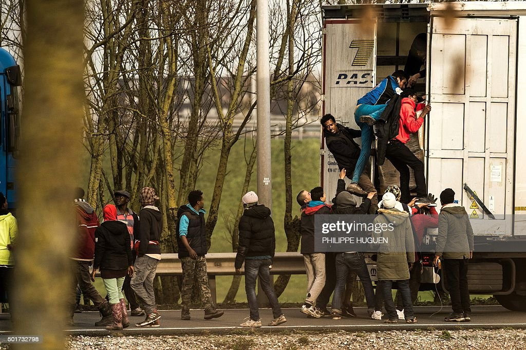 TOPSHOT - Migrants and refugees enter the trailer of a truck on December 17, 2015 on the site of the Eurotunnel in Calais. A growing number of migrants seeking to reach Britain are trying to leave from the Belgian port of Zeebrugge, prosecutors and police said on December 16, with people finding it increasingly hard to make the dangerous crossing from France's Calais. HUGUEN