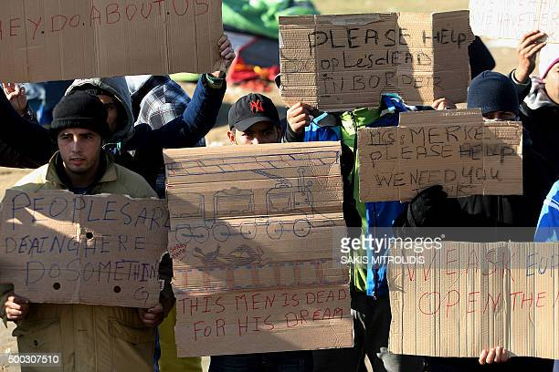 Migrants and refugees hold placards as they protest while waiting to cross the GreekMacedonian border near Idomeni on December 7 2015 Macedonia has...