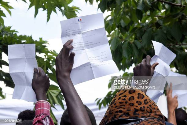 Migrants and refugees hold summons of the prefecture as they wait in front of the city hall to have their situation examined and to obtain emergency...