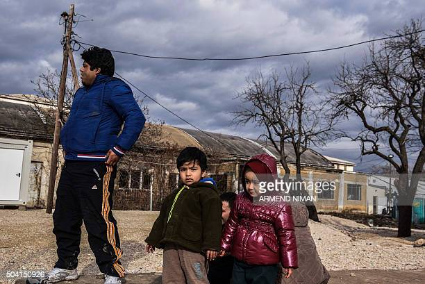 Migrants and refugees including children wait for a bus at a transit camp in the southern Serbian town of Presevo on January 9 2016 More than a...