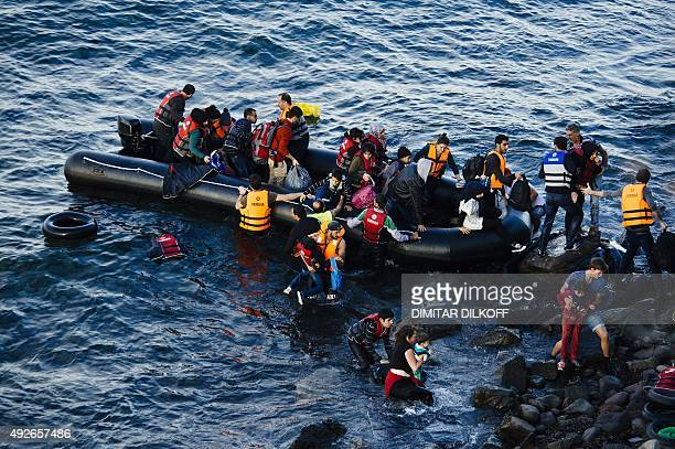 Migrants and refugees land on the Greek island of Lesbos after crossing the Aegean sea from Turkey on October 14 2015 More than 400000 refugees...