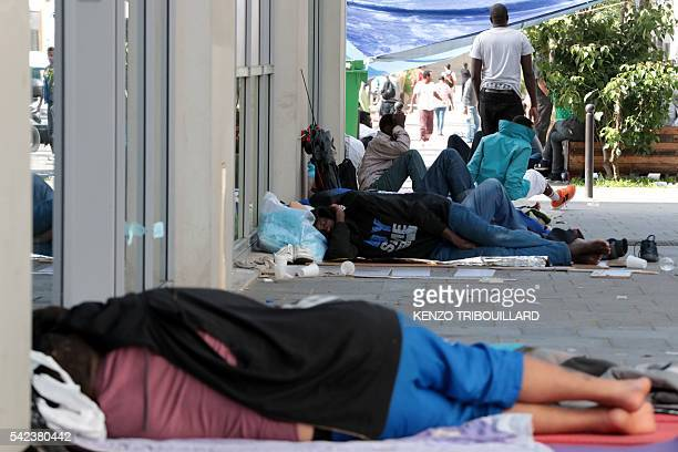 Migrants and refugees lie on the ground in a makeshift camp next to the Pajol hall place NathalieSarraute in Paris on June 23 2016 A migrants camp of...