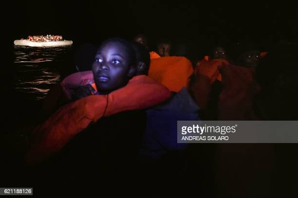 Migrants and refugees look on after boarding a small rescue boat during a rescue operation by the Topaz Responder ship run by the Maltese NGO Moas...
