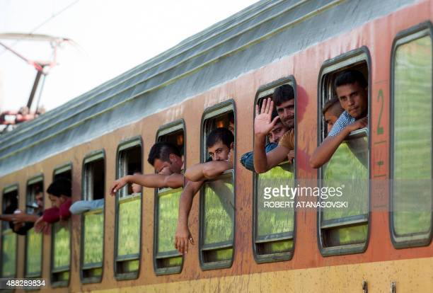 Migrants and refugees look out the window from a train heading to Serbia at the GreeceMacedonia border near the town of Gevgelija on September 15...