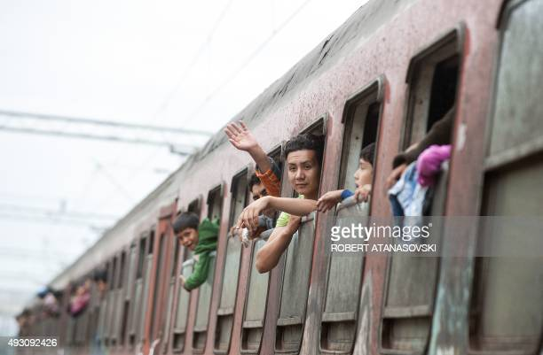 Migrants and refugees look through windows of a train heading to Serbia from the MacedonianGreek border near Gevgelija on October 17 2015 The...